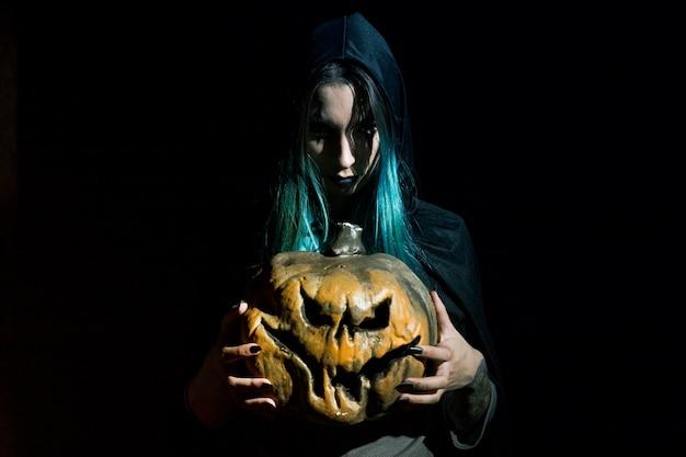 かぼちゃを飼っているフードの不気味な女性