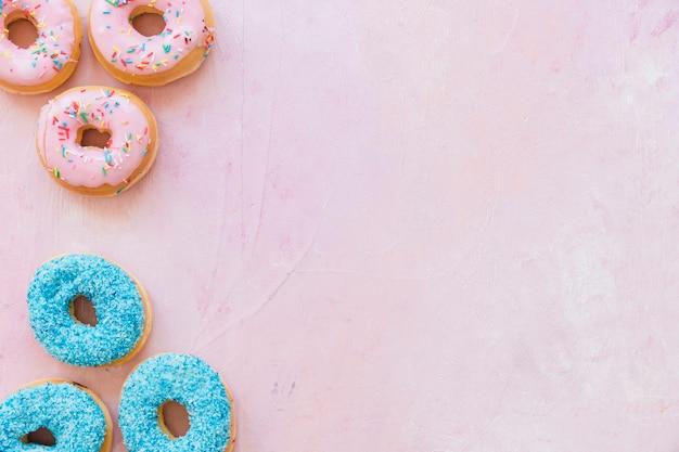 ピンクの背景に新鮮なおいしいドーナツの高い眺め