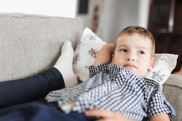 Расслабленный мальчик, лежащий на диване