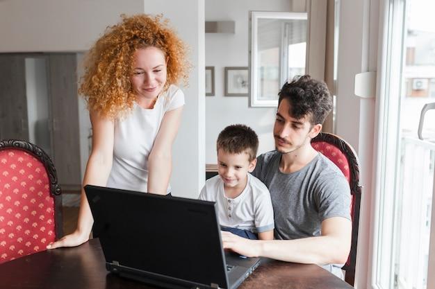 ラップトップでテーブルを見ている家族の肖像