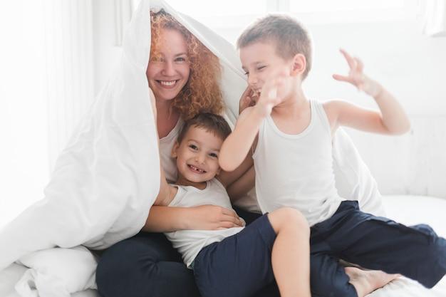Счастливая женщина, завернутая в одеяло, играющая с сыновьями