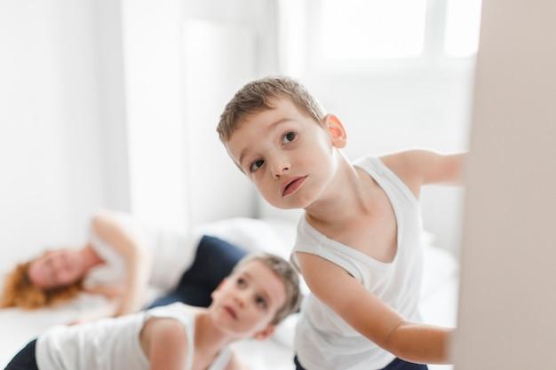 子供たちはベッドの上で眠っている母親の前景を覗き見る