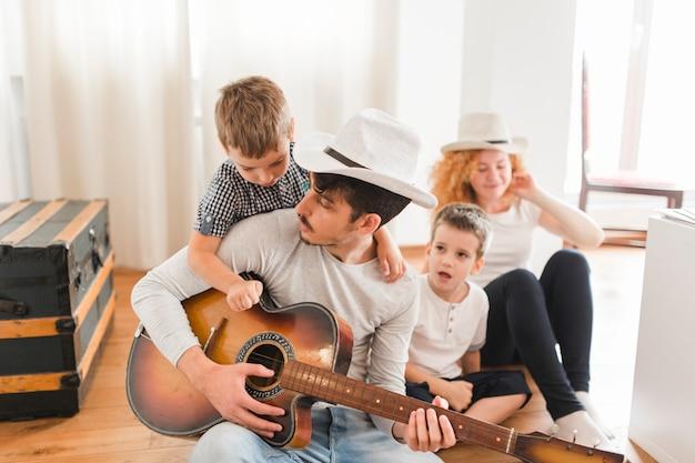 ギターを弾く彼の家族と一緒にハードウッドの床に座っている男