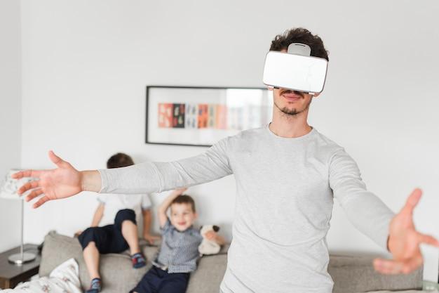 腕を伸ばしているバーチャルリアリティ・メガネを着ている若い男