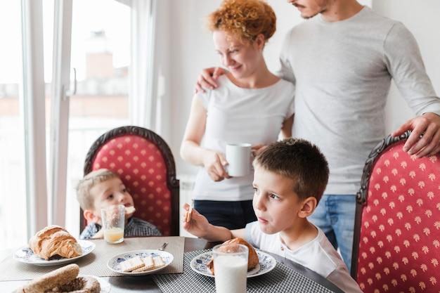 子供のそばに立っている親は朝食を取る