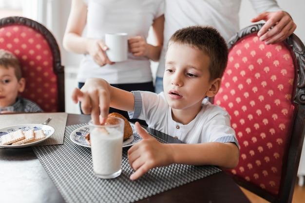 ミルクのガラスにビスケットを浸している男の子