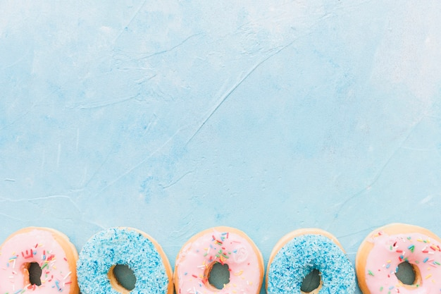 青い背景の下にカラフルなドーナツの高い角度のビュー