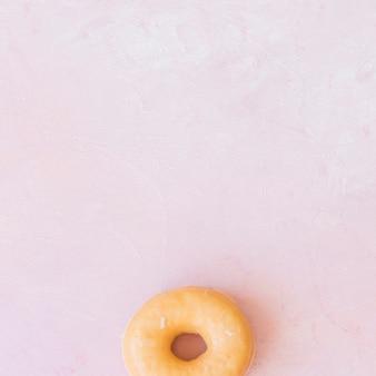 ピンクの背景にガラスのドーナツのオーバーヘッドビュー