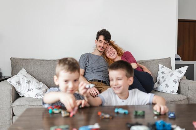 ソファに座っている両親の前で車のおもちゃで遊んでいる兄弟