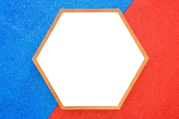 赤と青の背景に空の木製の六角形のフレーム