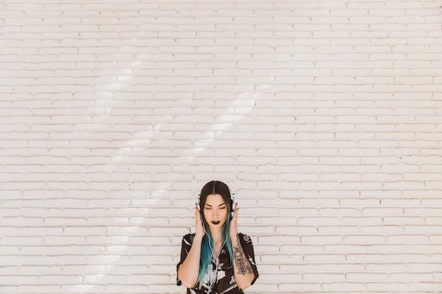 Крупный план молодой женщины, стоящей перед стеной