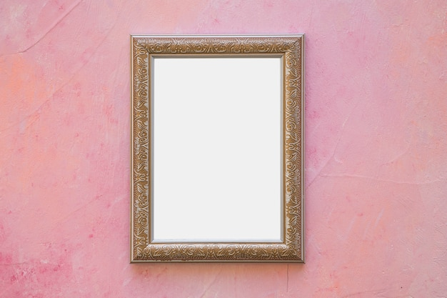 Золотая богато украшенная белая рамка на розовой стене