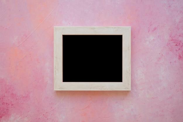 ピンクの塗られた背景に木製の黒板