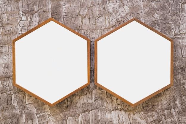 Две белые деревянные шестигранные рамки на обоях