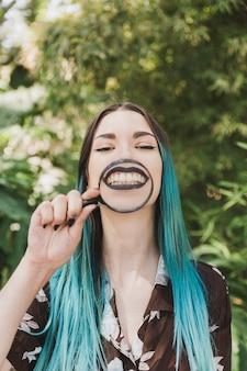 彼女の顔の上に虫眼鏡を持っている笑顔の若い女性