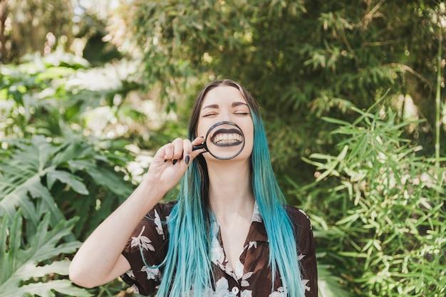彼女の口の前に虫眼鏡を保持している若い女性