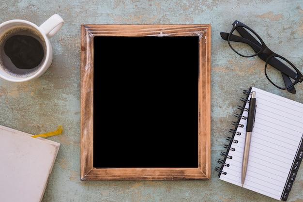 空白の画像フレーム。コーヒーカップと文房具、グランジの背景に