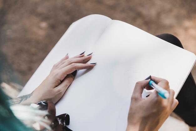女性の高い角度のビューノートブックで色鉛筆で花を描く