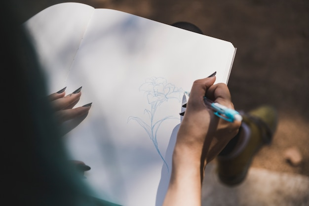 ノートパソコンに花を描く男の手のオーバーヘッドビュー