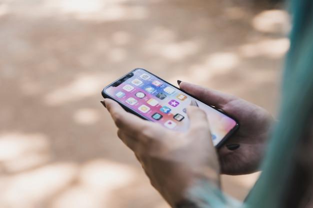 スクリーン、様々なアプリケーションアイコンと携帯電話を持っている女性の手のクローズアップ