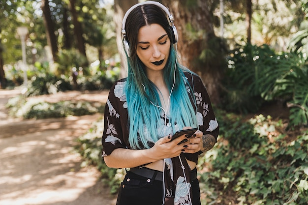 携帯電話を使って彼女の頭の上にヘッドフォンを持つ女性