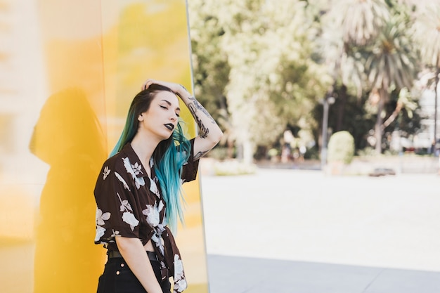 公園で彼女の頭の立っている上に手で若い女性のクローズアップ