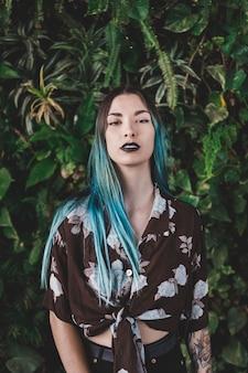 植物の前に立っている染めた髪の若い女性の肖像