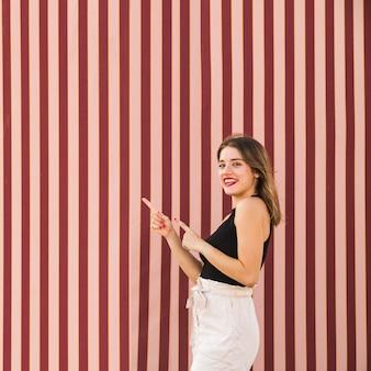 ストライプされた背景指す指の前に立っている笑顔の若い女性