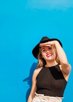 笑顔の若い女性は、太陽から目を守るために額に彼女の手を置く