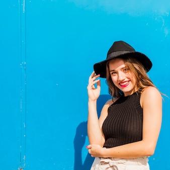 彼女の頭の上に黒い帽子で若い女性を笑顔