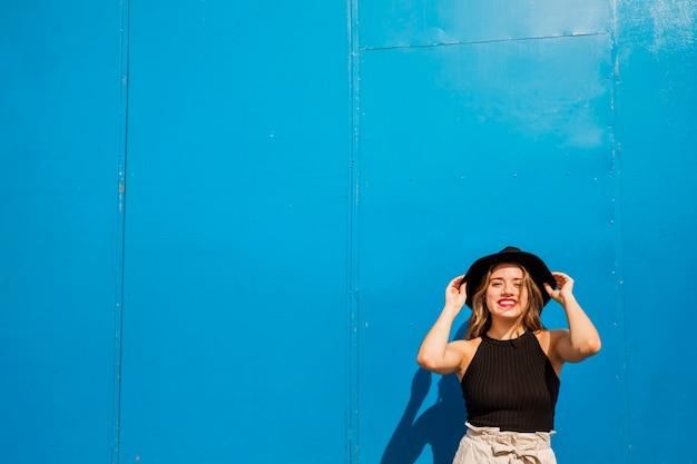 青い壁に立っている幸せな若い女性