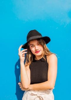 青い背景に黒い帽子をかぶっている笑顔の若い女性の肖像