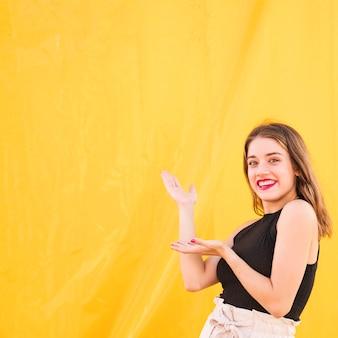 黄色の背景に提示する笑顔の若い女性