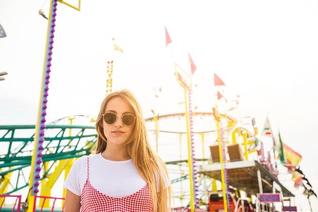 ローラーコースターの前に立つ美しい若い女性