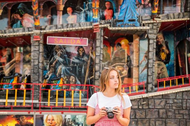 幽霊の家の前に立っている若い女性は、カメラを持っています。