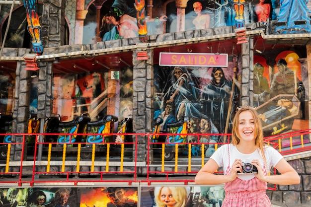 幽霊のある家の前に立っている笑顔の若い女性は、カメラを持っている