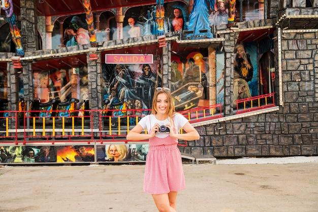 アミューズメントパークで幽霊のある家の前に立っている幸せな若い女性
