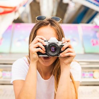 カメラで写真を撮っている若い女性