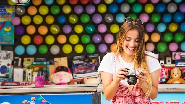 アミューズメントパークでカメラを見ている幸せな若い女性