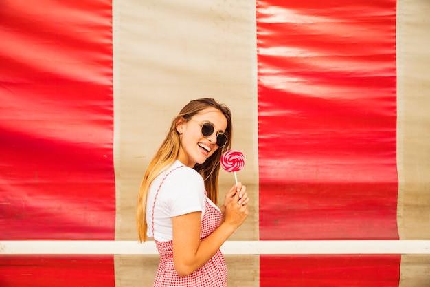 ロリポップでポーズを取る笑顔の若い女性