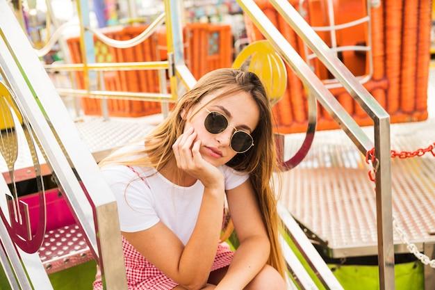 階段に座っているサングラスを着ている若い女性