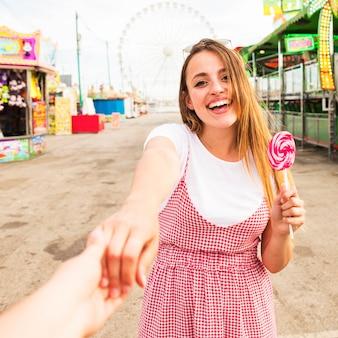 遊園地でロリポップを抱えている若い女性の手を持っている人のクローズアップ