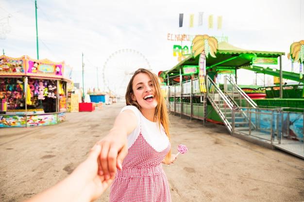 遊園地で彼女のボーイフレンドの手を握っている幸せな若い女性