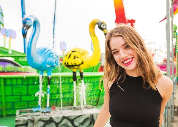 Портрет улыбающейся молодой женщины, стоя перед фонтаном