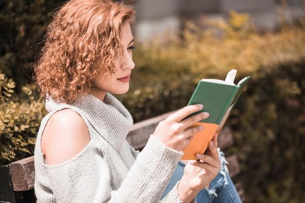 女性、注意深く、公園で本を読む