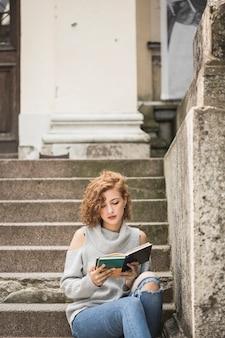 短い縮毛の本を読んでいる魅力的な女性