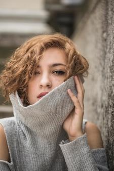 魅力的な若い女性は、長い髪を持ち、セーターの襟を上げる
