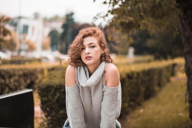 公共の庭のセーターの魅力的な女性
