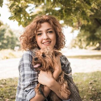 公園で犬と笑顔の女性
