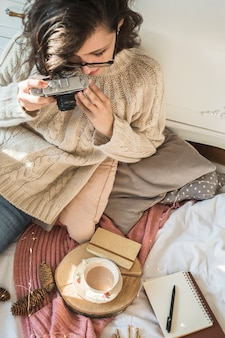 Молодая женщина с фото камеры, сидя на одеяло с подушками